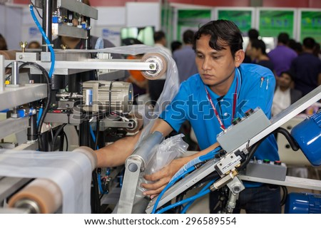 BANGKOK ,THAILAND - JULY 11: Unidentified people put a plastic roll into machine at InterPlas Thailand 2015 , on JULY 11, 2015 in Bangkok, Thailand.