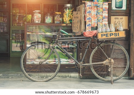 BANGKOK, THAILAND - July 1, 2017: Vintage style of Pepsi bottles stacked in plastic container on retro bike with retro shop background in Traditional Baan Bangkhen Museum in Bangkok Thailand.