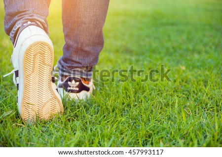 Bangkok,Thailand - July 25, 2016 : Woman walking with Adidas superstar shoes on green grass