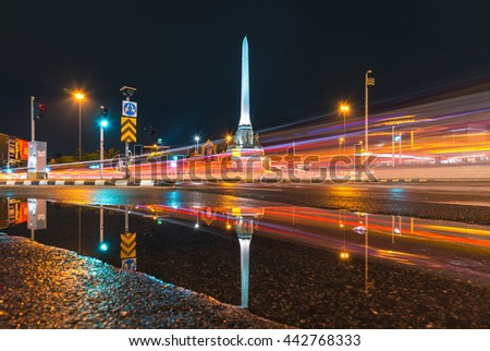 BANGKOK THAILAND - JUNE 23: Long exposure and water reflection for light trails of traffic around the victory monument at night after the rain on June 23, 2016 in Bangkok, Thailand