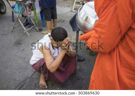 Bangkok, Thailand - June 28, 2015: People praying respect to monk on Bangkok street.  Roughly 95% of the Thai people are practitioners of Theravada Buddhism, the official religion of Thailand - stock photo