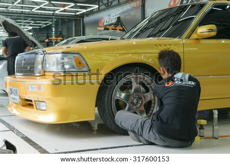 Bangkok, Thailand - June 28, 2015 : Unidentified car care staff cleaning and polishing the car wheel.