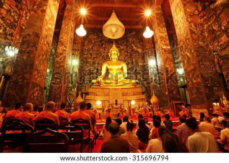 BANGKOK, THAILAND - MAR 31: Unidentified buddhist monks and People Praying at Wat Suthat Thepwararam on March 31, 2012 in Bangkok, Thailand. It is the respect and esteem of the people of Bangkok - stock photo