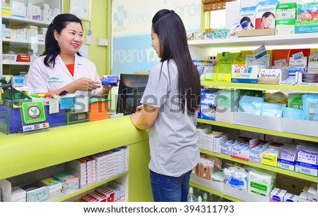 Bangkok,Thailand - MARCH 19:Friendly asian pharmacist in white lab coat giving young asian woman prescription drugs while standing in front of medicine counter on March 9,2016 in Bangkok,Thailand.