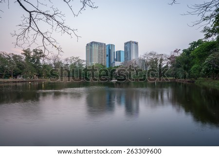 Bangkok, Thailand-March 16,2015 : The business skyscraper skyline is in Bangkok city downtown with reflection on lake looking from Railroad park in Bangkok,Thailand.