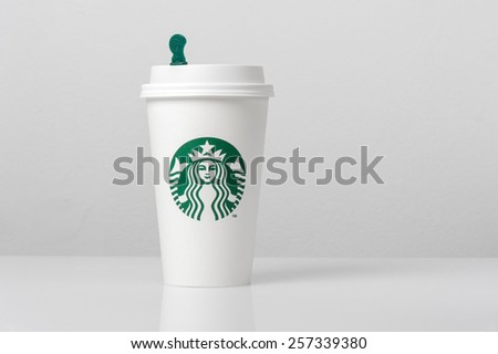BANGKOK, THAILAND - MARCH 03, 2015: White paper cup with Starbucks logo. Starbucks is the world's largest coffee house with over 20,000 stores in 61 countries. - stock photo