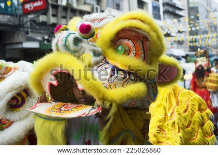 BANGKOK, THAILAND - MARCH 27, 2012:  Young boy are clothed in brightly coloured costumes  walking  in a lively procession throw Bangkok street on their way to Thai Buddhist temple. - stock photo