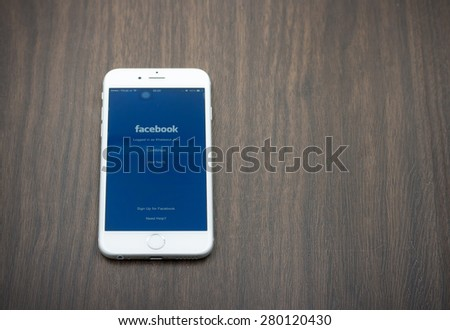 BANGKOK, THAILAND - MAY 7, 2015. Apple Iphone 6 in white color with facebook page laying on wooden table. - stock photo