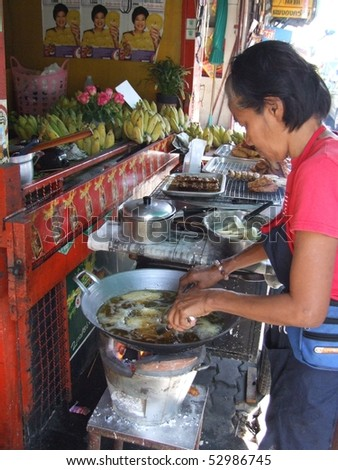 BANGKOK, THAILAND - MAY 18: Man preparing food in an open roadside restaurant May 18, 2005 in Bangkok.