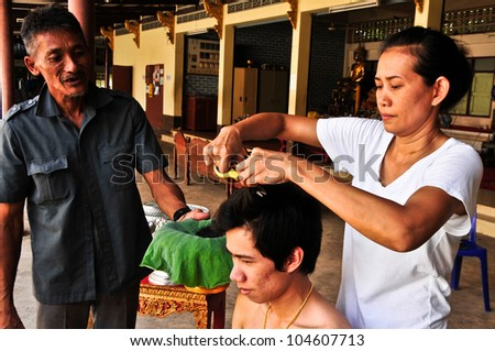 BANGKOK,THAILAND - MAY 26: Thai man during a Buddhist ordination ceremony. Close relatives cut pieces of his hair before it is shaved by a monk on May 26, 2012 in the Temple,Bangkok,Thailand.