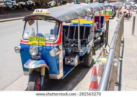 BANGKOK ,THAILAND - MAY 18 2015 : Tuk-tuk moto taxi on the street in the Pratunam area  in Bangkok. Famous bangkok moto-taxi called tuk-tuk is a landmark of the city and popular transport.