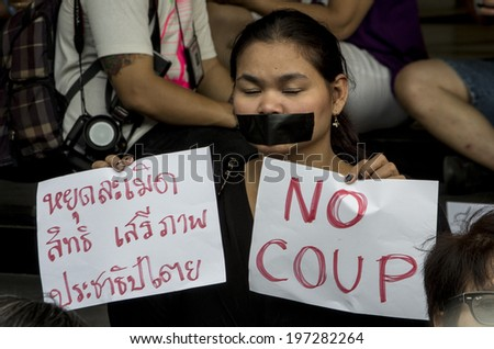 "BANGKOK, THAILAND - May 20, 2014: Unidentified demonstrators gagged themselves during a demonstrations on the first day of martial law. Left sign: ""Stop violating the right, freedom and democracy."" - stock photo"