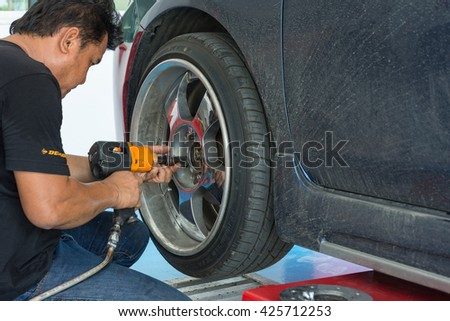 Bangkok, Thailand - May 20, 2016 : Unidentified serviceman checking suspension in a car at garage