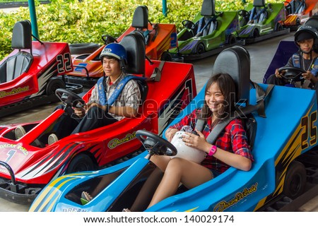 BANGKOK, THAILAND - 10 MAY 2013: unidentified Thai teens prepare to play go-kart at Dream World on May 10, 2013. Dream world is a famous amusement park in Thailand. - stock photo