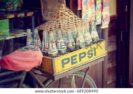 Bangkok, Thailand - May 7, 2017: Vintage retro style of Pepsi bottles stacked in grunge wooden container on retro bike with retro shop background in Traditional Baan Bangkhen Museum in Bangkok.