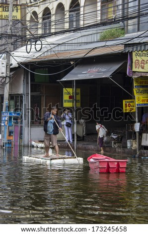 BANGKOK, THAILAND - NOV 5, 2011: A man with their transportation during a big flooding in Thailand. At Phongphet junction, Ngamwongwan road. - stock photo