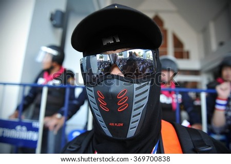 BANGKOK, THAILAND - NOV 27, 2013: A masked anti government protester stands guard outside at government building during a large rally. Protesters call for the government to be overthrown in a coup. - stock photo
