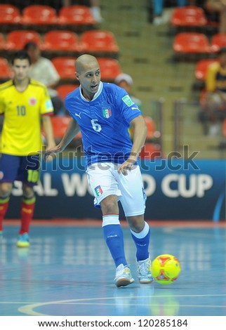 BANGKOK, THAILAND-NOV 18: Humberto Honorio of Italy (b) runs with the ball during the FIFA Futsal World Cup between Italy and Colombia at Indoor Stadium Huamark on Nov18,2012 in Bangkok,Thailand. - stock photo