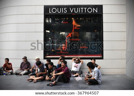 BANGKOK, THAILAND - NOV 10, 2013: People rest on a street outside a Louis Vuitton store. Louis Vuitton, founded in 1854, is a world leading luxury handbag brand with over 460 outlets in 50 countries.