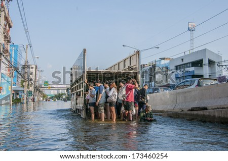 Bangkok - Thailand, Nov 6, 2011: People with their transportation during a big flooding in Thailand. At  Ngamwongwan road, nearby Phongphet junction. - stock photo
