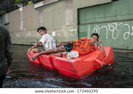 Bangkok - Thailand, Nov 6, 2011: People with their transportation during a big flooding in Thailand. At Soi Chaiyakiat, Ngamwongwan road. - stock photo