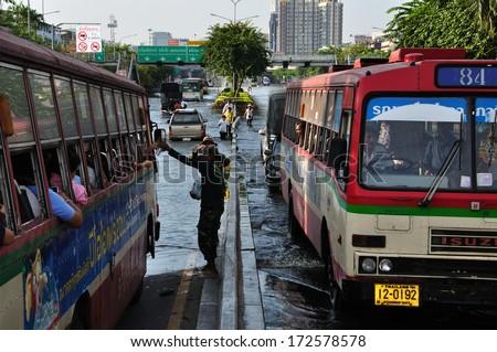 BANGKOK THAILAND- NOV 13: Unidentified people donate food and water for people on the bus on  flood street  on November 13, 2011 in Pra Pin Klao Brigde, Bangkoknoi, Bangkok, Thailand. - stock photo
