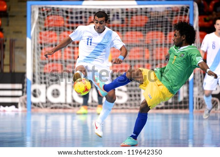 BANGKOK,THAILAND-NOVEMBER 09:Alan Aguilar (white)of Guatemala in action during the FIFA Futsal World Cup between Solomon Islands and Guatemala at Indoor Stadium Huamark on Nov9,2012 in,Thailand. - stock photo