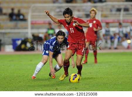 BANGKOK,THAILAND-NOVEMBER 24:Anucha Kitpongsri (r) of Thailand in action during the AFF SUZUKI CUP 2012 between Thailand and Philippines at Rajamangkala stadium on Nov 24,2012 inThailand. - stock photo