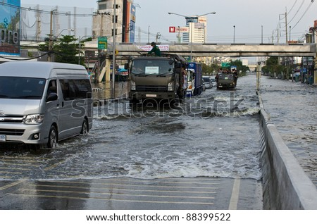 BANGKOK, THAILAND-NOVEMBER 8: Cars and trucks navigate through the flood after the heaviest monsoon rain in 20 years in the capital on  November 8, 2011   Ngam Wong Wan Road, Bangkok, Thailand.