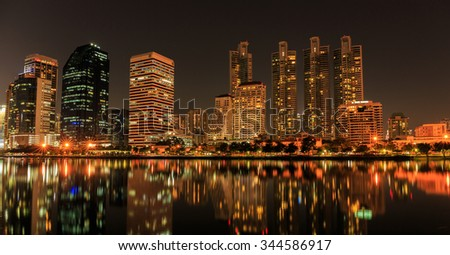BANGKOK, THAILAND-NOVEMBER 28 : The business skyscraper skyline are in Bangkok city downtown with reflection on wide lake in night time in Bangkok, Thailand on November 28,2015