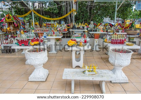 bangkok,Thailand - November 08,2014 :  Traditional thai spirit house with offering of flowers,doll and red drinks in Bangkok,Thailand. - stock photo