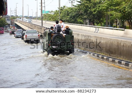 BANGKOK THAILAND - NOVEMBER 5 : Unidentified people sit and stand in car to escape rising flood waters at ladprao Road, in Bangkok, Thailand on Nov. 5, 2011.