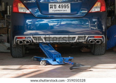 Bangkok, Thailand - November 21, 2015 : Unidentified serviceman checking suspension in a car at garage - stock photo