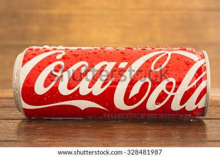 Bangkok, Thailand - Oct 13, 2015 : Coca-Cola soft drinks on the table with background with dark wood panels. Coca-Cola brand is one of the world famous soft drinks chains from USA.