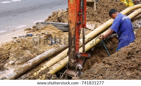 Bangkok, Thailand, 15 Oct 17 - male worker worked in digging street sidewalk ground tap water pipe system improvement work with help of small backhoe, blocking access by passersby in the area