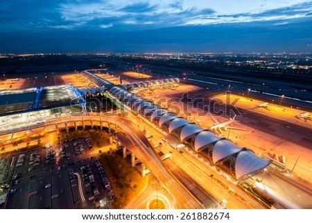 BANGKOK, THAILAND - OCTOBER 11: Airplanes and cars park at Suvarnabhumi airport at night with building and street lights on October 11, 2010 in Bangkok, Thailand. - stock photo