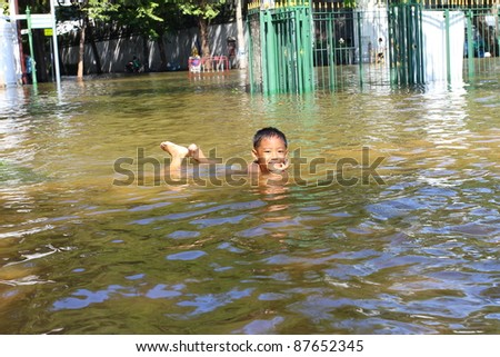 BANGKOK THAILAND - OCTOBER 29 : An unidentified boy plays in flood water on the road at Sanam luang on October 29, 2011, Bangkok, Thailand. - stock photo