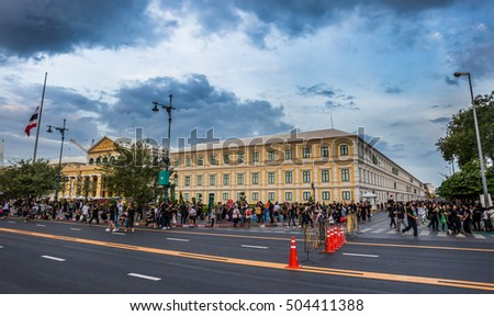BANGKOK,THAILAND-OCTOBER 21,2016:Crowds of mourners come for remember the memory and worship for Thai King Bhumibol Adulyadej with Ministry of Defense background on October 21,2016 in Bangkok,Thailand