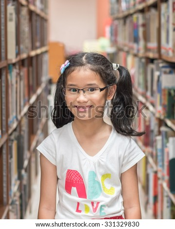 BANGKOK, THAILAND - OCTOBER 15, 2015: Happy Thai young school student child girl kid visiting university campus library standing among bookshelves found book resources was fun for reading experience  - stock photo