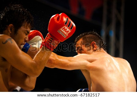 Bangkok, Thailand - October 12, 2010: Left jab from Caucasian muay thai fighter landing on face of Asian kickboxing opponent at amateur outdoor fight - stock photo