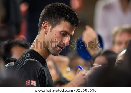 BANGKOK THAILAND OCTOBER 02:Novak Djokovic of Serbia signs signature to the fan during the Black to Thailand Nadal vs Djokovic exhibition match at Hua Mark Indoor Stadium on Oct 2, 2015 in,Thailand.