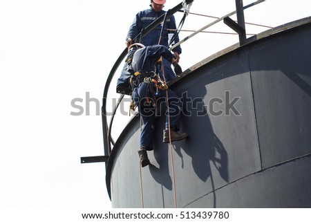 Bangkok Thailand - October 25th, 2016: Male worker rope access  inspection of thickness storage tank industry.