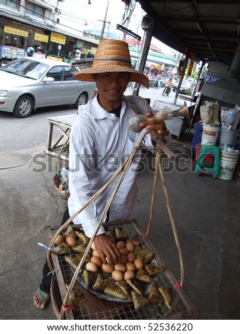 BANGKOK, THAILAND - OCTOBER 30: Thai man carries cooked eggs and wrapped sweet Thai food in baskets for sale to pedestrians October 30, 2005 in Bangkok.