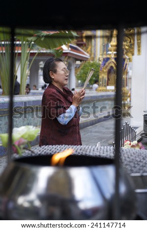 BANGKOK, THAILAND - OCTOBER 26, 2014: Thai woman prays at a Buddhist shrine in front of the Temple of the Emerald Buddha on the grounds of the Grand Palace. - stock photo