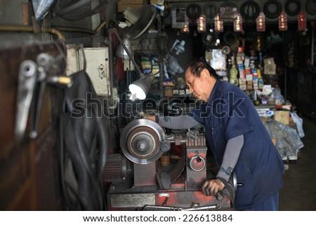 BANGKOK, THAILAND - OCTOBER 26, 2013: Unidentified auto mechanic fixing disc brake by mechanic machine in the garage. - stock photo
