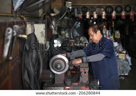 BANGKOK, THAILAND - OCTOBER 26, 2013: Unidentified car mechanic fixing disc brake by mechanic machine in the garage. - stock photo