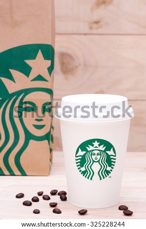 BANGKOK, THAILAND - OCTOBER 06, 2015: White cup of Starbucks coffee on wood board. Starbucks Corporation is an American global coffee company and coffeehouse chain based in Seattle, Washington. - stock photo