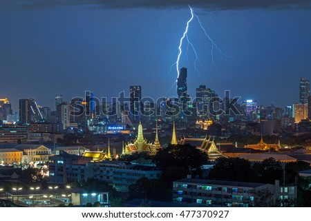 Bangkok, Thailand - September 2, 2016 : Lightning over the new, tallest, luxury, pixel-like building in Thailand. The Grand Palace and the Emerald Buddha Temple are located at the background