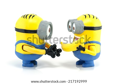 Bangkok,Thailand - September 13, 2014: Minion Dave give banana to Minion Stuart  toy character from Despicable Me 2 movie. There are plastic toy sold as part of the McDonald's Happy meals.