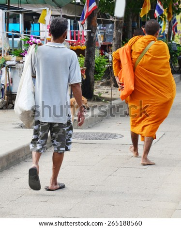 BANGKOK, THAILAND - SEPTEMBER 14 : People pray with monk and put food offerings to Buddhist alms bowl in morning time at small market on September 14, 2014 in Bangkok, Thailand.  - stock photo